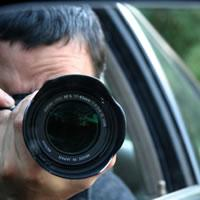 Image with man pointing camera lens out of car window.